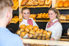 Two shopkeepers presenting a basket with buns to client Stock Photos