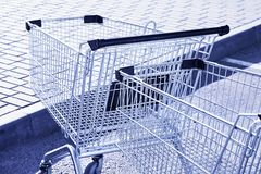 Shopping carts in a store parking lot. Blue toning Royalty Free Stock Photo