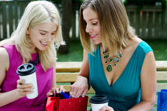 Two shopping examining purchases. Over coffee Royalty Free Stock Image