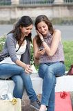 Two shopping girls in park with a mobile phone Royalty Free Stock Images