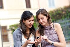Two shopping girls in park with a mobile phone Stock Photo
