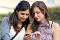 Two shopping girls in park with a mobile phone Stock Images