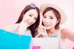 Two shopping woman selfie happily. Two shopping women selfie happily on the pink background royalty free stock photography