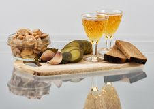Two short glasses of whisky and snack on a board. Two short glasses of whisky, bread, marinaded mushrooms and cucumber on a wooden board Stock Image