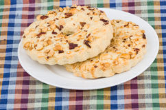 Two shortbreads rings with peanuts in plate on tablecloth Royalty Free Stock Photography