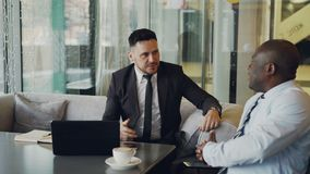 Two businessmaen in formal clothes shaking hands and taking seats on white leather armchairs to discuss their startup. Two shot of bearded Caucasian entrepreneur stock video footage
