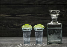 Two shot of  cold silver  tequila a black wooden background Royalty Free Stock Photos