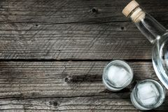 Two shot glasses with cold vodka or gin on wooden table, Royalty Free Stock Photo