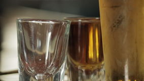 Two shot glasses filled next to beer close up. Video of two shot glasses filled next to beer close up stock video