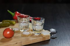 Two shot glasses of vodka on the cutting board royalty free stock images