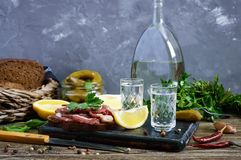 Two shot glasses of vodka with lemon slice, pickled cucumbers and rye bread with salted bacon. On the dark background. Traditional strong drink and appetizer Stock Photography