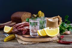 Two shot glasses of vodka with lemon slice, pickled cucumbers and rye bread with salted bacon on the dark background. Traditional strong drink and appetizer Royalty Free Stock Photo