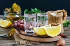 Two shot glasses of vodka with lemon slice, pickled cucumbers and rye bread with salted bacon. On the dark background. Traditional strong drink and appetizer Royalty Free Stock Photography