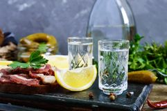 Two shot glasses of vodka with lemon slice, pickled cucumbers and rye bread with salted bacon. On the dark background. Traditional strong drink and appetizer Stock Photos