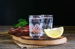 Two shot glasses of vodka with lemon slice and rye bread with salted bacon on the dark background. Traditional strong drink. Close-up Royalty Free Stock Images