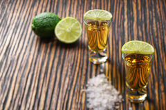 Two shot of gold tequila on a  brown wooden background ,selectiv Stock Images