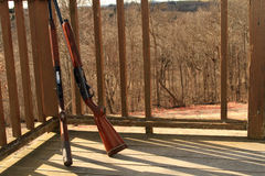 Two shot guns at sporting clay range. Two shot guns leaning against railing at sporting clay range, trap shooting range with broken clays in background Stock Image