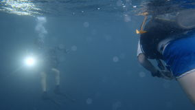 Two scuba divers underwater. A two shot of two scuba divers. One scuba diver has a light on towards the camera stock footage