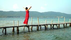 Two a shot in video. Phu Quoc Island. The woman costs on a pier with the straightened hands. The woman looks at open. Two a shot in video. Beautiful woman stock video