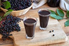 Two glasses of black elder syrup with fresh elderberries Stock Photos
