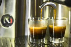 Two shots of espresso being drawn Royalty Free Stock Photo