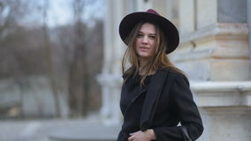 Two shots of fashionable glamorous young girl with long hair, purple hat and black coat walks looking to camera. Fashion stock video