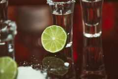 Two shots of tequila with lime and salt on a wooden table bar on the background of bright lights of the bar Stock Photo