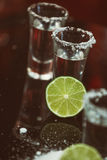 Two shots of tequila with lime and salt on a wooden table bar on the background of bright lights of the bar Stock Photos