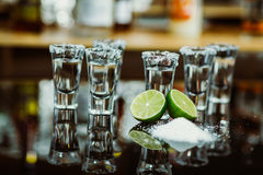 Two shots of tequila with lime and salt on a wooden table bar on the background of bright lights of the bar Stock Image