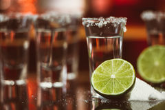 Two shots of tequila with lime and salt on a wooden table bar on the background of bright lights of the bar Stock Photography