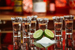 Two shots of tequila with lime and salt on a wooden table bar on the background of bright lights of the bar Royalty Free Stock Photography