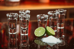 Two shots of tequila with lime and salt on a wooden table bar on the background of bright lights of the bar Royalty Free Stock Images