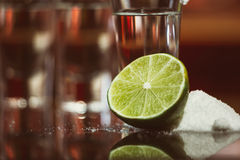 Two shots of tequila with lime and salt on a wooden table bar on the background of bright lights of the bar Royalty Free Stock Photo