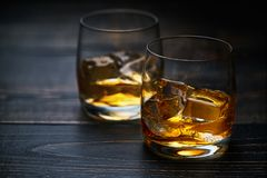 Two shots of whiskey  with ice  on a  black wooden table Royalty Free Stock Photography