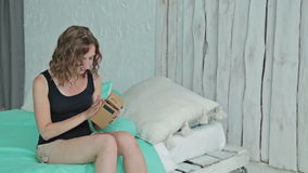 Two shots. Young curly woman using Virtual Reality Glasses and lying in the bed. Two shots. Woman's hands holding Google cardboard. Young curly woman using stock footage