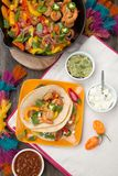 Two Shrimp Fajitas. With bell pepper, onion, and jalapeno in a plate and shrimp fajitas in a cast iron skillet ready to be served. Guacamole, salsa, and Royalty Free Stock Photo