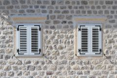 Two shuttered windows in the stone wall of the house Stock Image