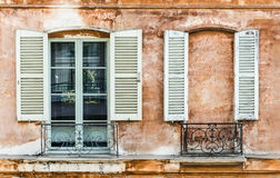 Two shutters on window and wall. Two old shutters on a window and a wall built to mask a window. Decoration on old Franch building Royalty Free Stock Photo