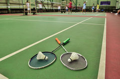 Two shuttlecocks on rackets in the badminton court Royalty Free Stock Photos