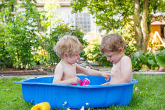 Two sibling boys having fun with water in summer Stock Image