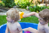 Two sibling boys having fun with water in summer Stock Images
