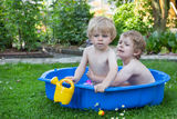 Two sibling boys having fun with water in summer Royalty Free Stock Photo