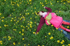 Two sibling children lying on spring meadow with green grass and yellow dandelions flowers Royalty Free Stock Photos