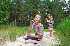 Two sibling children playing with soap bubbles on Stock Image