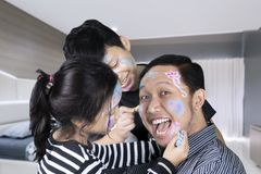 Two sibling doing face painting to their father Stock Image