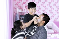 Two sibling doing face painting to their father Royalty Free Stock Image