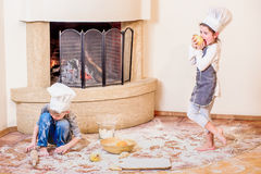 Two siblings - boy and girl - in chef`s hats near the fireplace sitting on the kitchen floor soiled with flour, playing with food Royalty Free Stock Photo