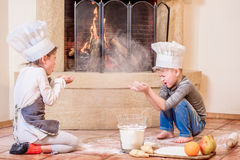 Two siblings - boy and girl - in chef`s hats near the fireplace sitting on the kitchen floor soiled with flour, playing with food Stock Photos