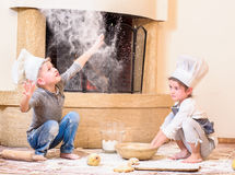 Two siblings - boy and girl - in chef`s hats near the fireplace sitting on the kitchen floor soiled with flour, playing with food Royalty Free Stock Photos