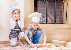 Two siblings - boy and girl - in chef`s hats near the fireplace sitting on the kitchen floor soiled with flour, playing with food Royalty Free Stock Images
